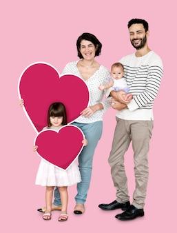 Heureuse famille tenant des icônes en forme de coeur
