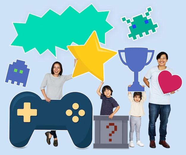 Heureuse famille tenant des icônes de jeu