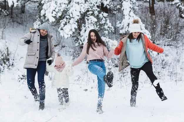 Heureuse famille en train de botter la neige