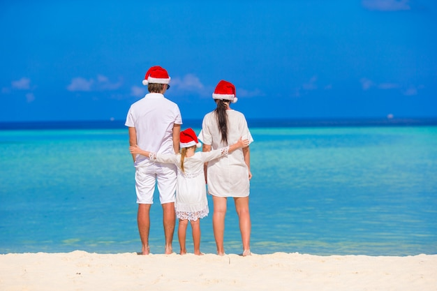 Heureuse famille de trois personnes à santa hats pendant des vacances tropicales