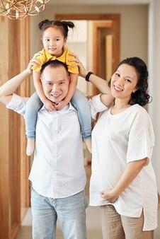 Heureuse famille vietnamienne: mère souriante touchant son ventre quand son mari fait le ferroutage à sa petite fille