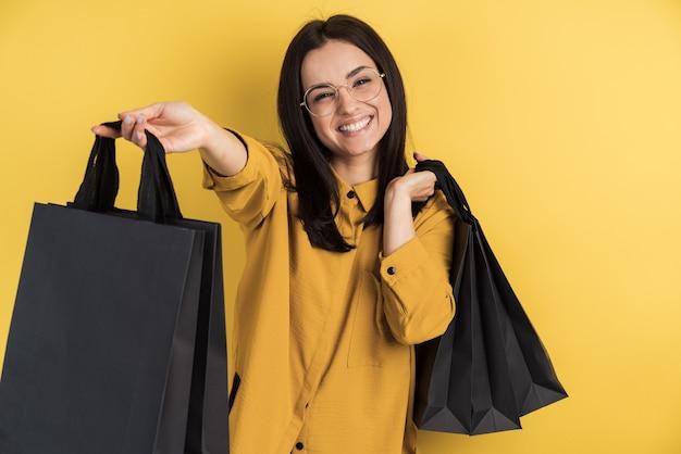Heureuse femme accro du shopping élégant dans des verres tenant des sacs sur le mur de studio orange isolé