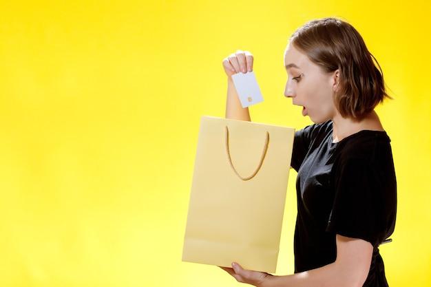 Heureuse femme accro du shopping posant des sacs à provisions et une carte de crédit sur fond jaune.