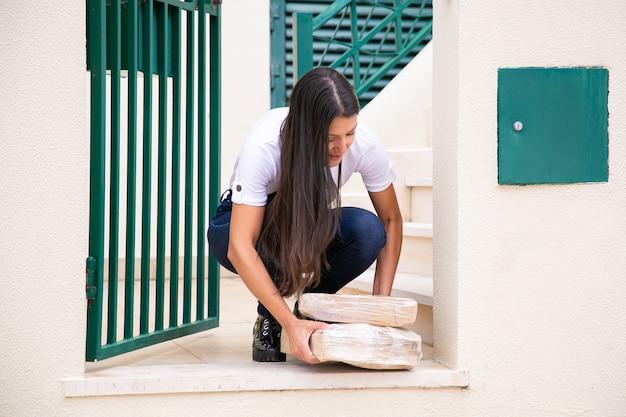 Heureuse femme accroupie et prenant ses colis à l'entrée. vue avant du client de la boutique en ligne recevant la commande dans des boîtes en carton et portant des jeans et une chemise. service de livraison et concept d'achat en ligne