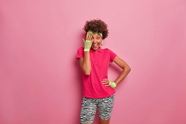 Heureuse femme active avec une coiffure afro regarde à travers les doigts, vêtue de vêtements confortables et décontractés, a un sourire positif sur le visage
