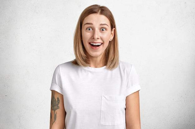 Heureuse femme adorable positive avec une expression excitée, reçoit une surprise inattendue d'un ami vêtu de vêtements décontractés