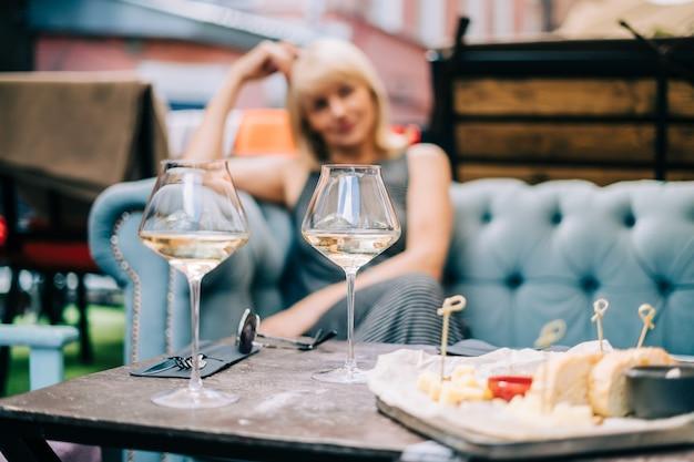 Heureuse femme adulte assise sur un canapé dans un bar à l'extérieur avec des verres à vin et un restaurant flou