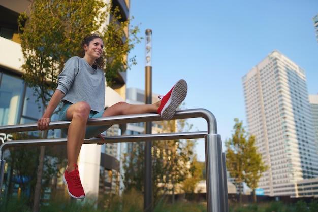 Heureuse femme adulte moyenne faisant de l'exercice sur des barres parallèles à l'extérieur en ville, concept de mode de vie sain.