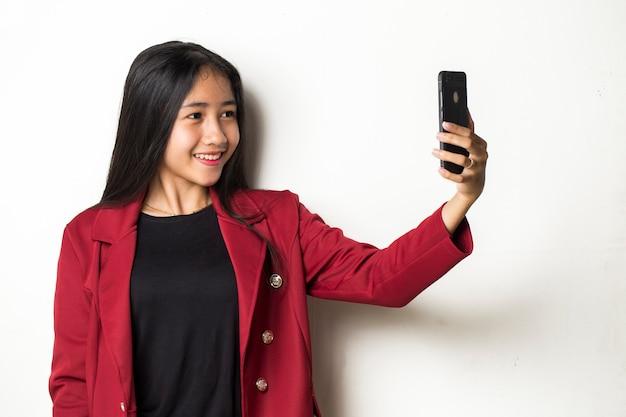 Heureuse femme d'affaires asiatique avec téléphone mobile faisant selfie. portrait de jeune fille souriante posant sur fond blanc