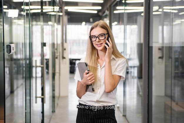 Heureuse femme d'affaires ayant une conversation téléphonique agréable. sourire, femme, blanc, bureau, chemisier, parler cellule, et, apprendre, bonnes nouvelles. concept de bonne nouvelle
