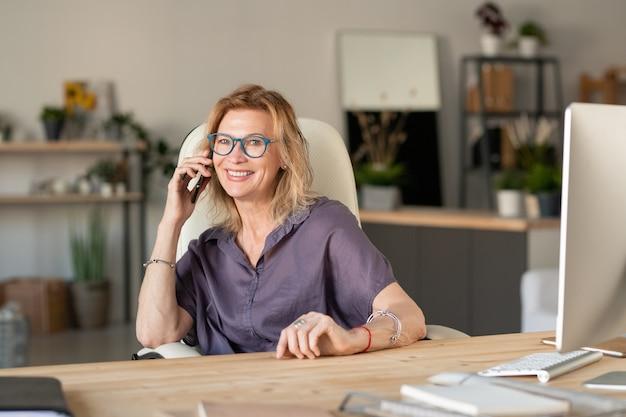 Heureuse femme d'affaires blonde mature en tenue décontractée assis par 24 devant l'ordinateur dans le salon tout en parlant sur smartphone