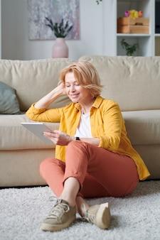 Heureuse femme d'affaires blonde avec tablette numérique, passer du temps à la maison et regarder un film en ligne ou parler à quelqu'un via le chat vidéo