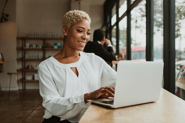 Heureuse femme d'affaires dans un café à l'aide de son ordinateur portable