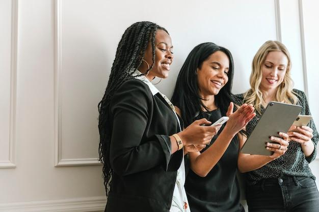 Heureuse femme d'affaires diversifiée à l'aide d'une tablette numérique