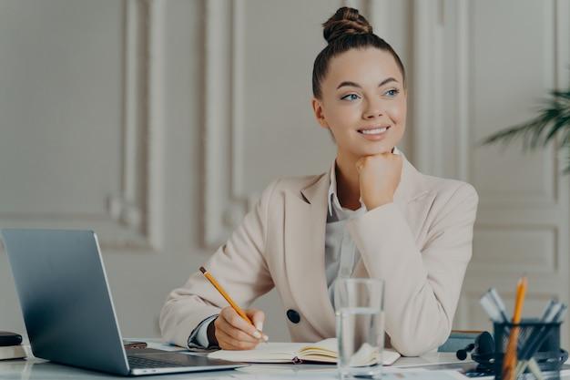 Heureuse femme d'affaires élégante en tenue classique travaillant à distance sur un ordinateur portable, joyeuse employée regardant de côté et souriante, prenant des notes tout en étant assise au bureau. concept d'emploi et de profession