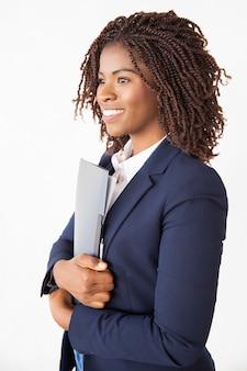 Heureuse femme d'affaires joyeuse tenant dossier avec des documents
