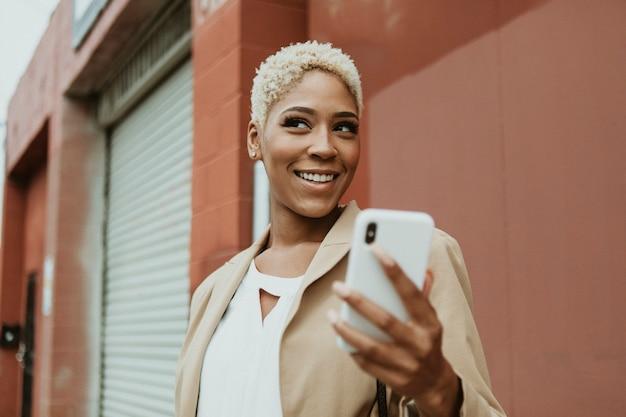 Heureuse femme d'affaires noire à l'aide de son smartphone