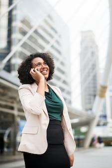 Heureuse femme d'affaires parlant au téléphone