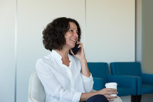 Heureuse femme d'affaires parlant sur une cellule