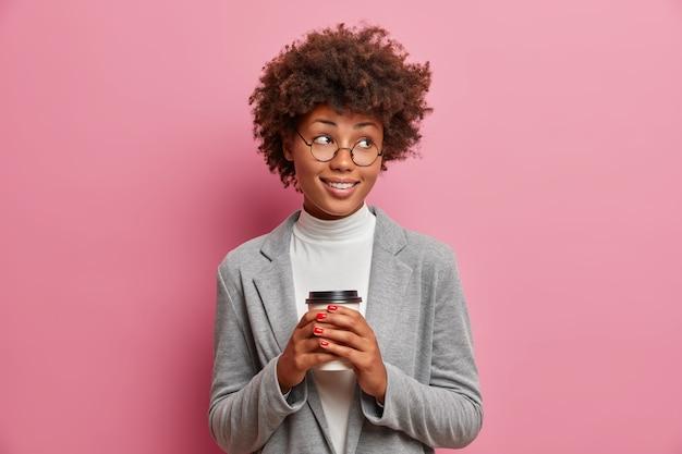 Heureuse femme d'affaires à la peau sombre insouciante tient une tasse de café, regarde de côté et sourit largement, porte des vêtements élégants