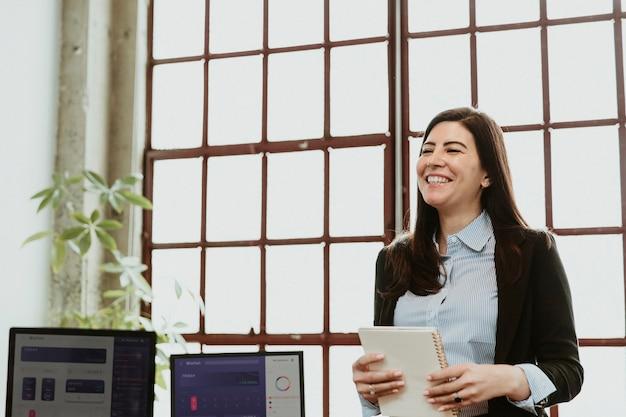 Heureuse femme d'affaires présentant lors d'une réunion