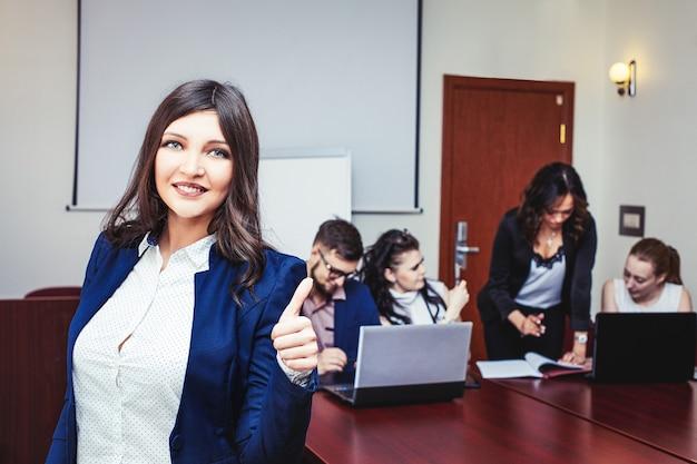 Heureuse femme d'affaires prospère au bureau avec des collègues en arrière-plan.