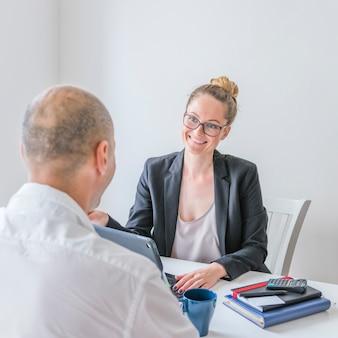 Heureuse femme d'affaires en regardant son partenaire au bureau