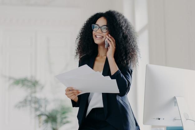 Heureuse femme d'affaires réussie porte des lunettes, détient des documents, passe un appel téléphonique