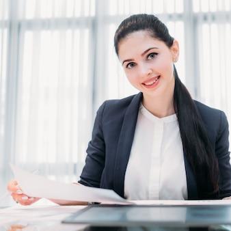 Heureuse femme d'affaires souriante dans l'espace de travail de bureau
