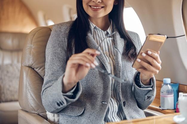 Heureuse femme d'affaires souriante en jet privé