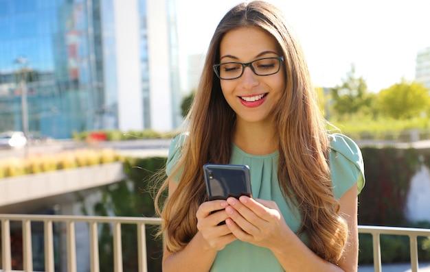 Heureuse femme d'affaires souriante avec téléphone portable dans la rue.