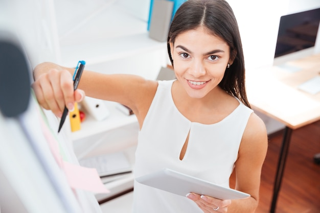 Heureuse femme d'affaires tenant une tablette et écrivant sur un tableau blanc