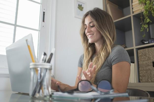 Heureuse femme d'affaires travaillant sur ordinateur portable à la maison. jeune femme travaillant avec un sourire. belle pigiste travaillant à l'aide d'un ordinateur portable au bureau à domicile