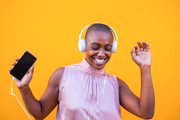 Heureuse femme africaine ou américaine dansant et vibrant seule avec son téléphone à la main avec des écouteurs