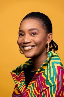 Heureuse femme africaine avec des boucles d'oreilles dorées