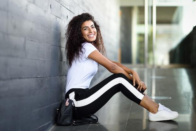 Heureuse femme africaine avec une coiffure frisée noire, assis sur le sol urbain.