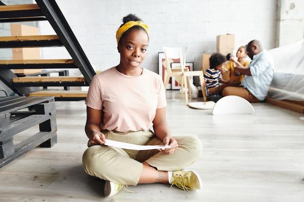 Heureuse femme africaine avec du papier assis sur le sol du salon contre l'escalier, jeune homme et deux enfants assemblant des meubles