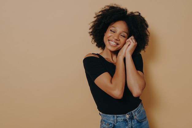 Heureuse femme africaine mignonne des années 20 aux cheveux bouclés, gardant les mains près du visage et les yeux fermés, souriant agréablement tout en rêvant de quelque chose de bien, isolée sur fond beige. concept d'émotions humaines