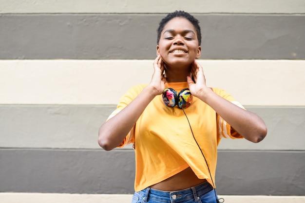 Heureuse femme africaine souriante sur un mur urbain les yeux fermés, portant des vêtements décontractés et des écouteurs.