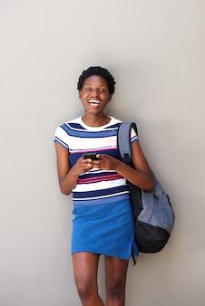 Heureuse femme africaine avec téléphone portable et rire sur fond gris
