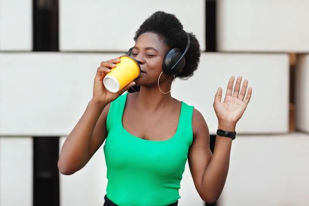 Heureuse femme africaine tenant un café dans une tasse jetable, écoutant la mélodie agréable dans les écouteurs et dansant. l'heure de la musique. espace pour le texte.