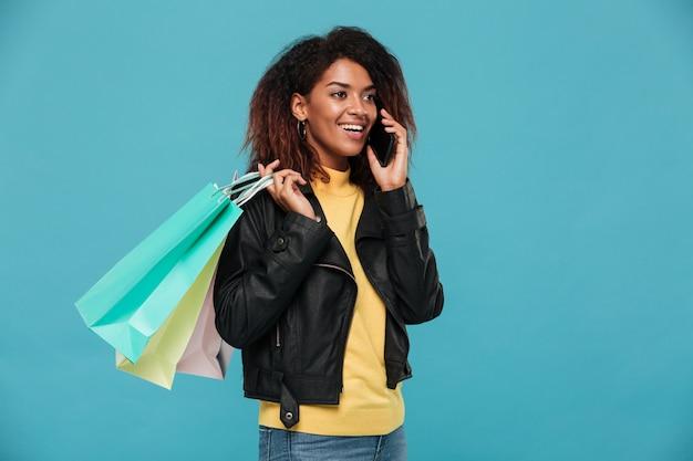 Heureuse femme africaine tenant des sacs à provisions parler par téléphone.