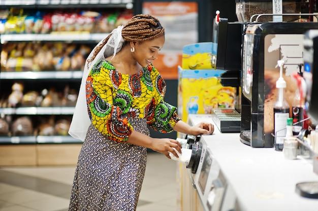 Heureuse femme africaine en vêtements traditionnels et voile à la recherche de produit à l'épicerie, faire du shopping dans un supermarché. afro femmes noires faisant du café à la machine à café.
