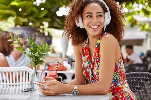 Heureuse femme afro-américaine aime écouter de la musique dans des écouteurs, tient un téléphone intelligent et regarde positivement loin, s'assoit dans un café en plein air