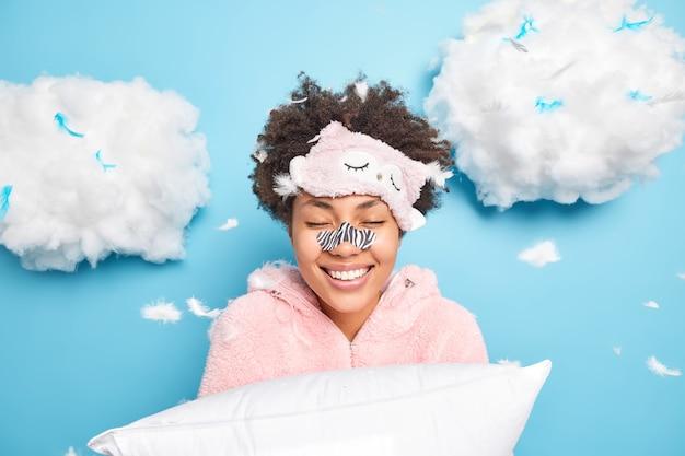 Heureuse femme afro-américaine bouclée se débarrasse des points noirs sur le nez à l'aide d'un patch spécial veut avoir une peau propre et impeccable sourit doucement habillée en pyjama tient des poses d'oreiller autour de plumes volantes