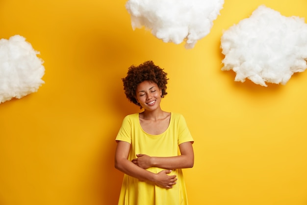 Heureuse femme afro-américaine embrasse le ventre de femme enceinte, exprime son amour pour l'enfant à naître, sourit joyeusement, profite des derniers mois de grossesse, isolé sur un mur jaune. la future mère embrasse le ventre