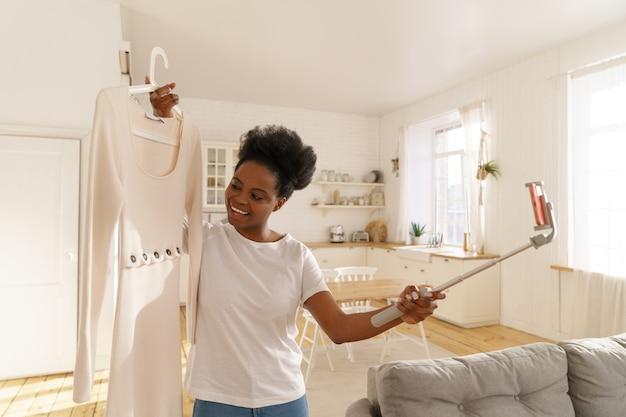 Heureuse femme afro-américaine montrant la mode robe d'été par téléphone portable sur trépied en ligne à la maison