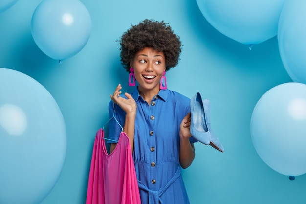 Heureuse femme afro-américaine positive choisit l'extérieur pour un rendez-vous, tient des chaussures bleues à talons hauts et une robe rose sur des cintres, se prépare à faire la fête et à la célébration, pose sur un mur bleu avec des ballons gonflés