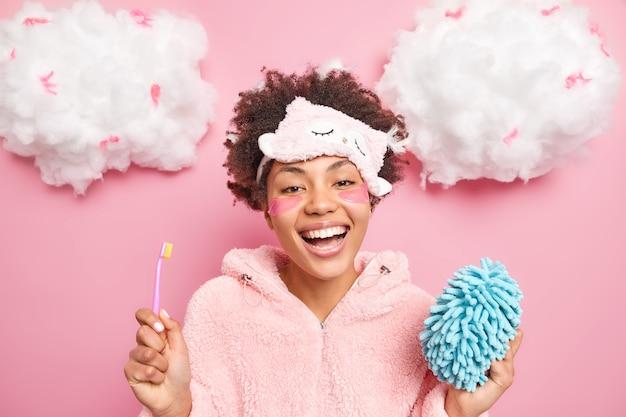 Heureuse femme afro-américaine sourit largement apprécie le bon matin se brosse les dents et subit la beauté applique les procédures de coussinets tient la brosse à dents et l'éponge de bain porte un masque de sommeil sur le front
