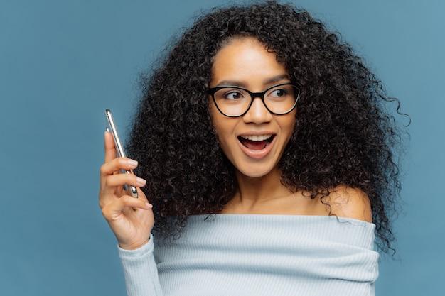 Heureuse femme afro-américaine surprise sur son téléphone portable, interagissant par appel téléphonique